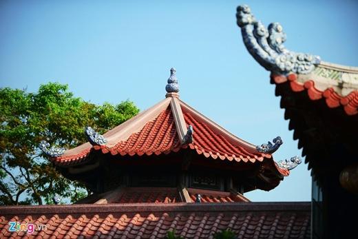 Tám góc mái cong vút như mái đình làng được đắp những nụ mây hóa rồng màu thiên thanh rất bắt mắt. Mái nhà lợp ngói ống âm dương lối cổ tráng men màu son nhẵn bóng.
