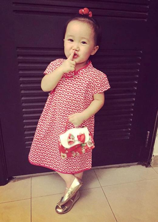 Không chỉ mặc đẹp, Luna còn biết cách tạo dáng sành điệu trước ống kính. Nhờ đó, những tấm ảnh ngẫu hứng do mẹ Linh Nga ghi vội được cộng đồng mạng yêu thích. Trong ảnh là bộ váy cách điệu gam màu đỏ được mix hợp tông cùng túi xách. Giày ánh bạc là xu hướng hot của mùa hè 2015.