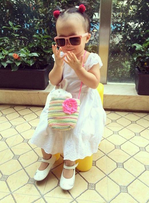 Cô nhóc diện váy trắng, giày hợp tông và túi xách len làm điểm nhấn.