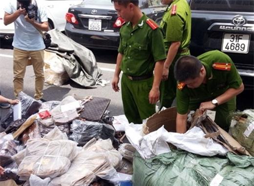 Lực lượng chức năng thu giữ hàng hiệu giả - Ảnh: Quang Minh