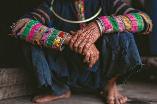 Người dân tộc với bộ quần áo sờn rách, đôi tay nhăn nheo chai sạn và bàn chân trần.