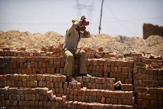 Những công nhân đang làm việc tại công trình xây dựng phải chống chọi với cái nóng lên đến 50 độ C