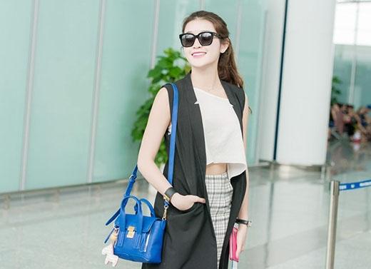 Thời trang sân bay của Á hậu Huyền My luôn được đánh giá cao bởi sự năng động, trẻ trung. Cô chọn phối chân váy bút chì caro xẻ cao gợi cảm kết hợp cùng crop top trắng và áo blazer khoác ngoài tone đen.