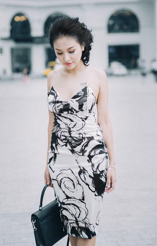 MC Thanh Vân Hugo diện đầm hai dây xẻ ngực sâu gợi cảm với họa tiết hoa hồng đen làm điểm nhấn trên nền trắng.