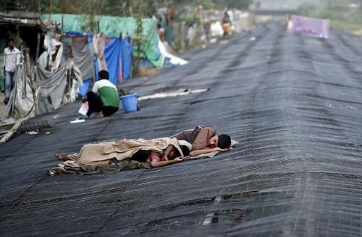 """. """"Chúng tôi hoặc phải làm việcdù sinh mạngbị đe dọa, hoặc sẽkhông có gì đểăn"""", nông dân Narasimha ở huyệnNalgonda,bang Andhra Pradesh nói. Trong ảnh, người dân nghèo phải ngủ trên nóc các tòa nhà có bóng mát để tránh nóng."""