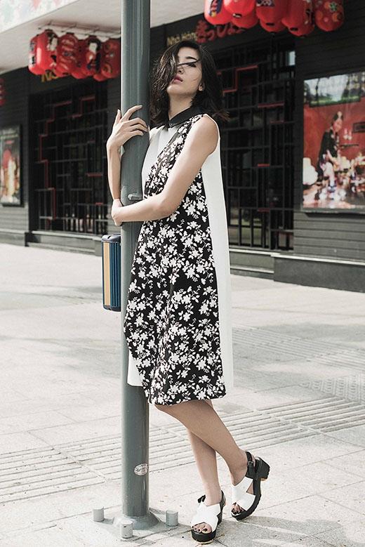 Huỳnh Nu chọn phối váy chữ A trắng cùng giày sandal đế thô hợp mốt. Điểm nhấn của bộ váy nằm ở chi tiết vải hoa được bố trí bất đối xứng bên thân trái.