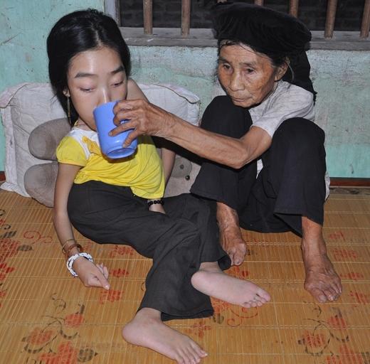 Dù đã hơn 90 tuổi nhưng cụ bà Lê Thị Ty vẫn chăm sóc hai cháu bị bệnh hàng ngày
