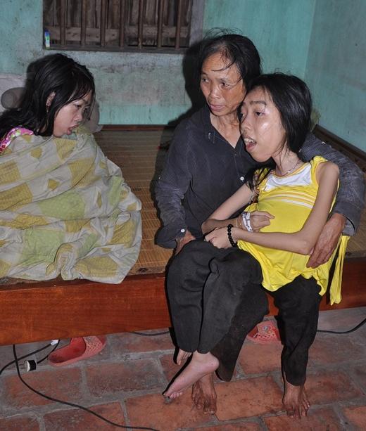 CôXuânbên hai người con gái bị bệnh của mình. Ảnh: DT