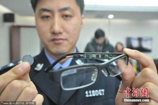 Chiếc mắt kính có thể scan và truyền hình ảnh từ phòng thi ra bên ngoài khi bấm vào đồng xu nhỏ được gắn ở bên trong.