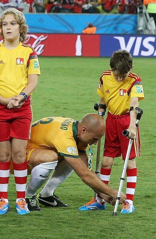 Cầu thủ Mark Bresciano đang giúp một cậu nhóc đi nạng buộc lại dây giày.