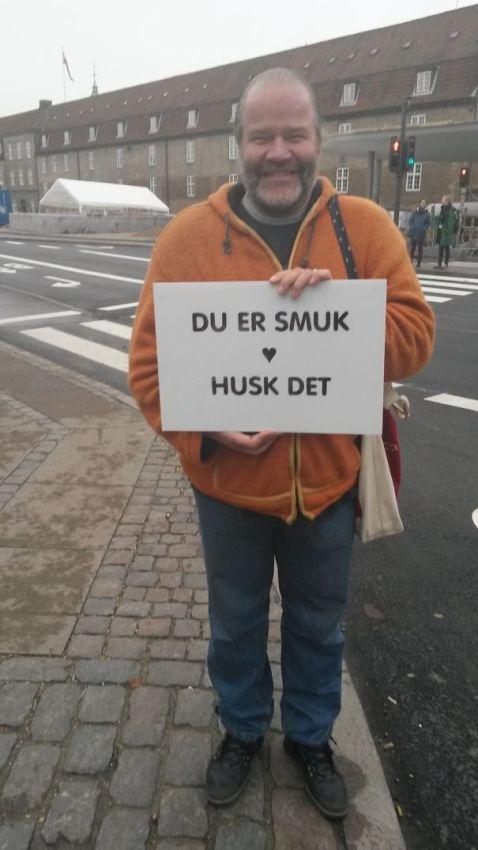 Một người đàn ông ở một ngã tư tại Copenhagen tươi cười với tấm bảng: Bạn rất xinh đẹp! Đừng bao giờ quên điều đó!