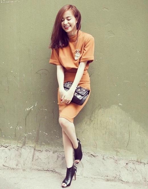 Chân váy, áo phông cùng tone cam đất được tạo điểm nhấn với túi xách đen và giày da hở mũi cùng tone.