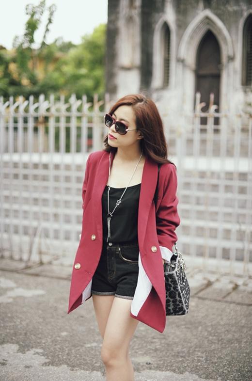 Gợi cảm nhưng kín đáo khi phối áo hai dây cùng tone đen với short jeans và khoác thêm măng tô tone đỏ rượu chát bên ngoài.