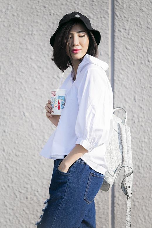 Sự kết hợp hài hòa, độc đáo giữa yếu tố hiện đại của chiếc áo sơ mi phom rộng cùng chiếc quần jeans baggy denim rách cổ điển. Chiếc balo tone xám như một phụ kiện đi kèm vừa tạo nên vẻ năng động cho trang phục.