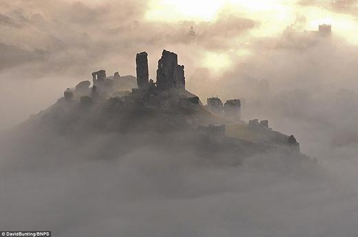 """Thoắt ẩn thoắt hiện trong làng sương mờ ảo là lâu đài Corfe nằm giữa đồi Purbeck thuộc vùng Dorset, mang đến một vẻ ma mị đến """"nổi da gà"""". Nơi đây từng là căn cứ quân sự """"sống sót"""" trong cuộc nội chiến của nước Anh, nhưng phần nào bị hư hại vào năm 1646 do sự tàn phá bởi các nghị viên."""