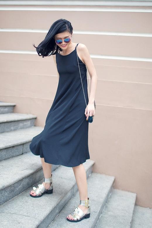 Chiếc váy đen mốt ngủ được cô kết hợp cùng kính mặt gương, sandal chiến binh ánh kim cùng túi đeo chéo vai nhỏ xinh.