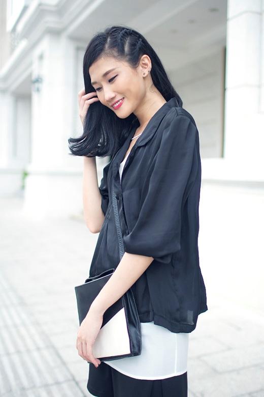 Chiếc túi xách đi kèm cũng hài hòa với trang phục với hai mảng màu trắng đen chia nhau theo đường chéo.
