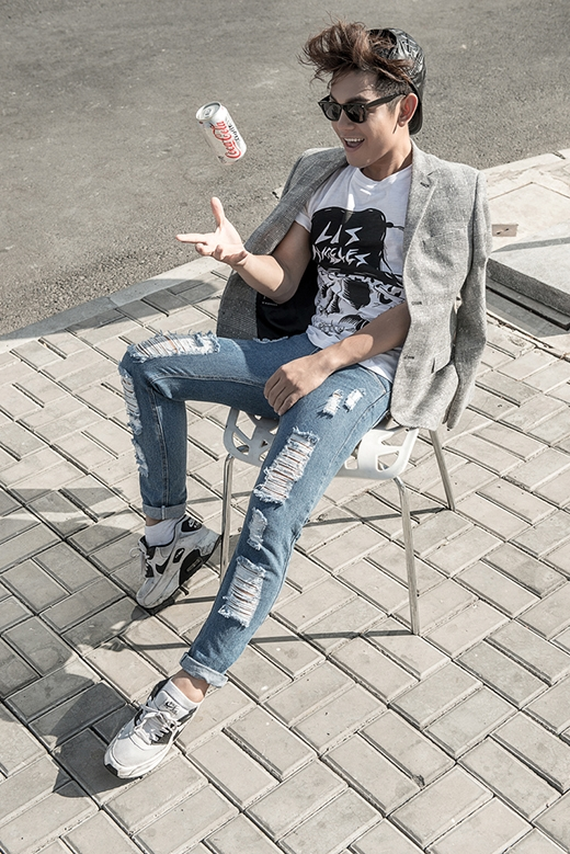 Nét bụi bặm cá tính trong chiếc quần jeans rách kết hợp áo phông họa tiết phối hợp khá hài hòa với sự thanh lịch, chỉn chu của chiếc áo vest kẻ caro tone xám ghi trầm ấm. Sơn Ngọc Minh kết hợp phụ kiện cùng mũ lưỡi trai màu đen với chất liệu da cùng mắt kính gọng to cổ điển.