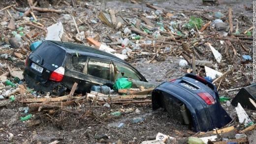 Nước lũ quật đổ nhiều cây cối và cuốn phăng những gì trên đường đi của nó. Trong hình là hai chiếc xe hơi bị cuốn trôi đi trong dòng lũ lớn.