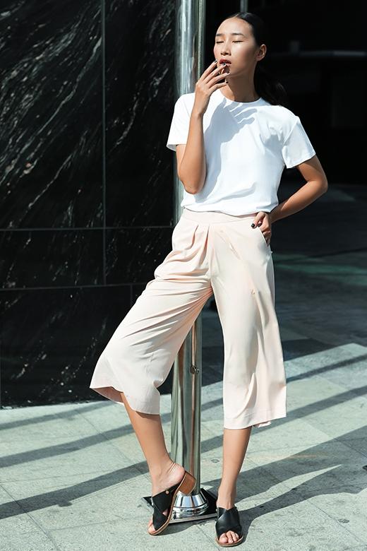 Chiếc quần culottes màu hồng pastel được chân dài khéo léo phối cùng chiếc áo tròng cổ tay ngắn gam xanh xám.