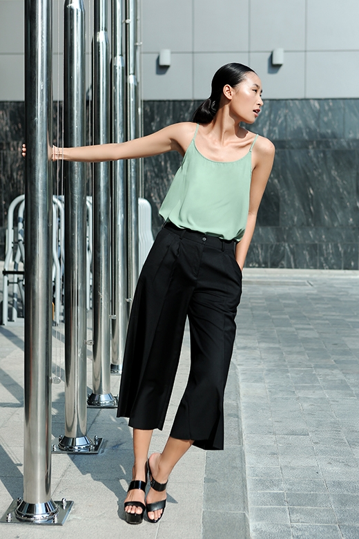 Bộ trang phục kết hợp hài hòa giữa nét gợi cảm của chiếc áo hai dây gam màu pastel cùng sự thanh lịch, hợp mốt của chiếc quần culottes màu đen với những đường xếp li đối xứng tinh tế.