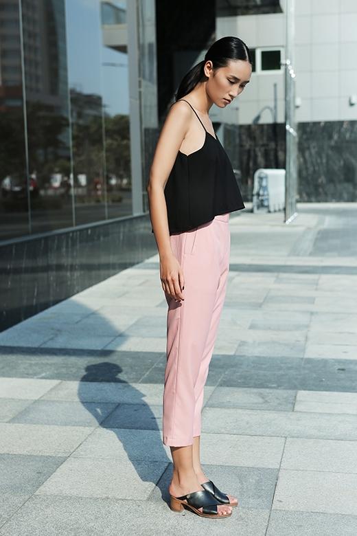 Sự kết hợp tương phản làm nổi bật cả hai thành phần của trang phục: crop top đen cùng quần ống suông gam hồng pastel dịu ngọt, nữ tính.