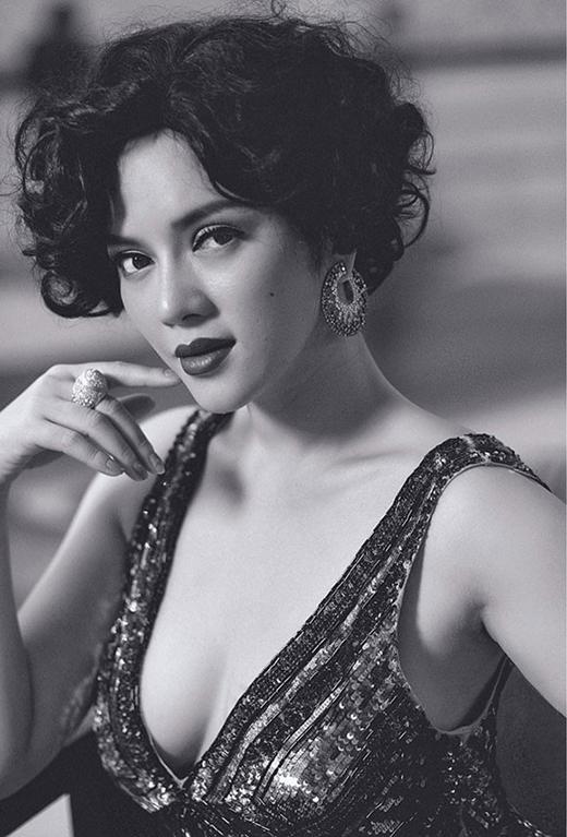 Hình ảnh của một nữ danh ca những năm 80 tái hiện hoàn hảo trong chiếc đầm quây ánh kim xẻ ngực sâu cùng mái tóc xoăn bồng xòe.