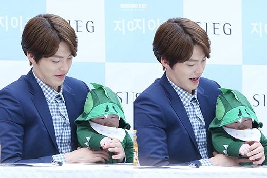Đây là hình ảnh ghi điểm của Kim Woo Bin trong mắt công chúng khi anh vừa ký tên vừa trông em bé. Chỉ vậy thôi cũng đủ thấy được nam diễn viên yêu thích trẻ con đến dường nào.