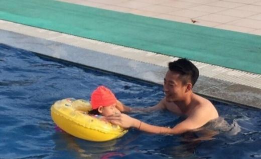 Anh dạy con gái tập bơi.
