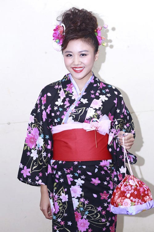 Những bông hoa màu tím hồng nổi bật trên nền đen của bộ kimono mà Văn Mai Hương diện. Cô chọn kiểu tóc đánh xù và cài hoa giả cùng màu với họa tiết trên trang phục.
