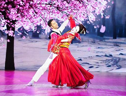 """Kết hợp họa tiết màu vàng kim trên nền đỏ của trang phục giúp Ninh Dương Lan Ngọc tỏa sáng trên sân khấu """"Bước nhảy Hoàn vũ 2015"""". Với phom dáng dài kín đáo nhưng phần chân váy cũng được cách điệu bằng những chi tiết dún bèo."""
