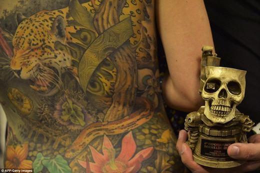 Một thợ xăm với chiếc cúp giải thưởng hình xăm đẹp mắt nhất vừa giành được.