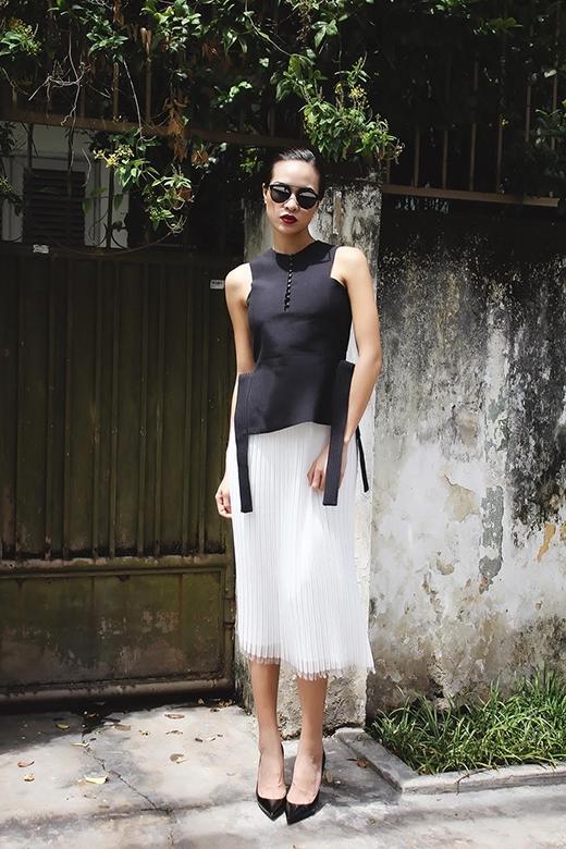 Chiếc áo đen không tay với điểm nhấn bởi hai chi tiết hình cung đối xứng hai bên vạt áo được kết hợp cùng chân váy voan xếp li màu trắng.