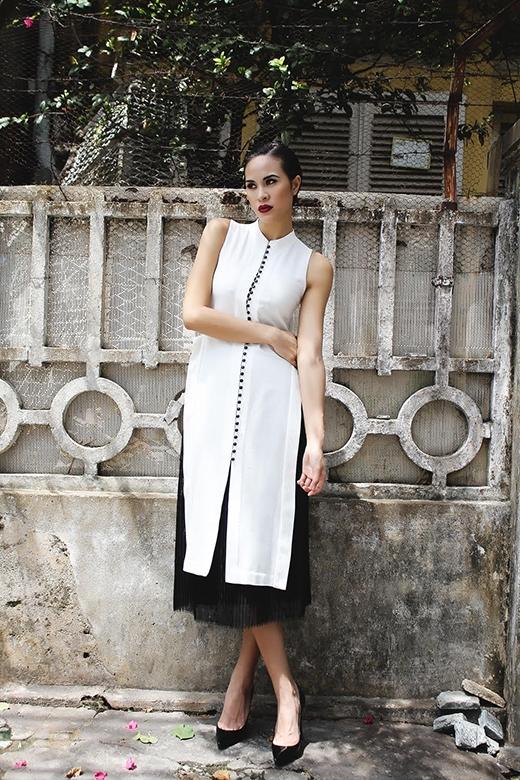 Hàng cúc đen trải dài trên thân áo tạo nên sự liên kết về màu sắc với chân váy.