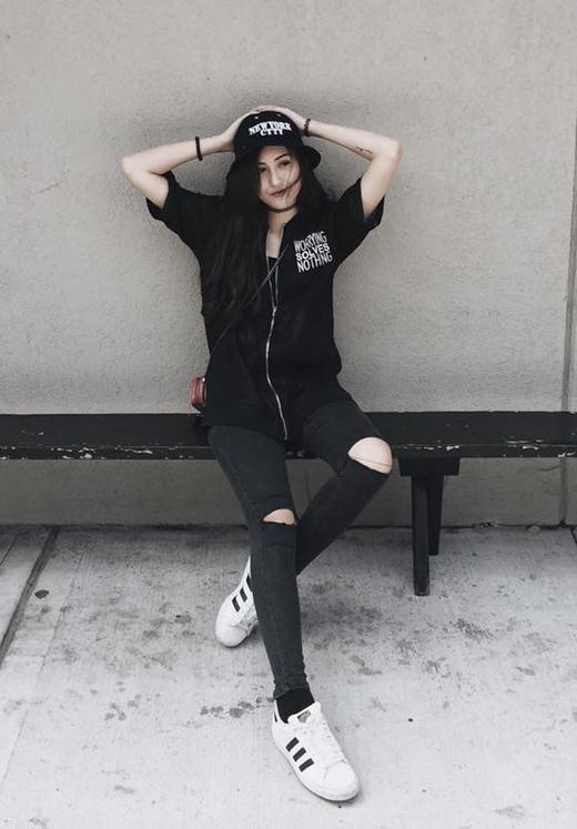 Vẫn với món phụ kiện này, hotgirl gốc Hà thành lại diện cả cây đen cực chất với áo dáng rộng cùng quần jeans bó sát. Cô đội mũ fedora và đi giày thể thao năng động, cá tính.