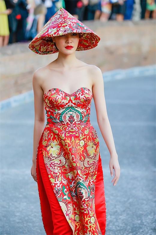 Thiết kế với tone màu đỏ nổi bật giúp tôn lên làn da trắng hồng của Hoa hậu Việt Nam 2008. Cô còn đội chiếc nón lá khá độc đáo được phủ gấm đồng điệu với bộ trang phục.
