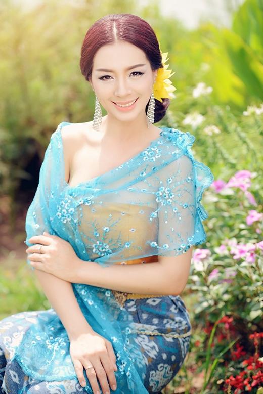 Cô chọn bộ trang phục với gam màu xanh biển dịu mát tạo điểm nhấn bởi phần thân áo màu vàng đồng.