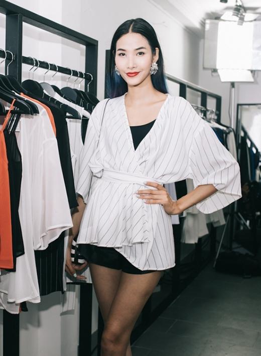 Chiếc áo khoác trắng của Hoàng Thùy được tạo điểm nhấn bởi những đường kẻ sọc đen mảnh mai. Cô diện bộ trang phục theo mốt giấu quần với hai gam màu trắng - đen tương phản.