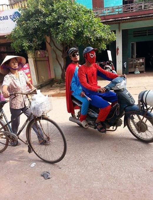 Người nhện (Spider Man) đang chở một siêu nhân khác bằng xe máy cà tàng