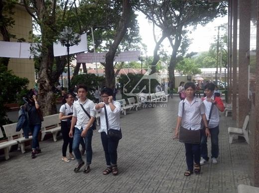 Các thí sinh đang ngồi dưới sân trường ôn bài thi bất ngờ mưa dông kéo đến
