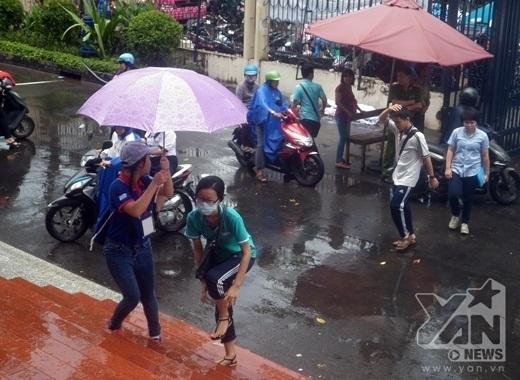 Hình ảnh các bạn tình nguyện viên hỗ trợ các thí sinh đến phòng thi trong mưa dông