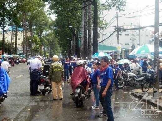 Cảnh sát giao thông cũng đội mưa điều tiết các phương tiện quanh điểm thi
