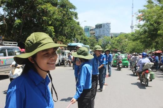 Sinh viên tình nguyện đứng giữa trời nắng hơn 40 độ c để phân luồng giao thông ở Hà Nội. Ảnh: DT