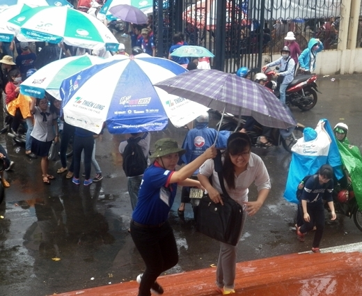 Tận tình cầm dù che không cho mưa ướt thí sinh