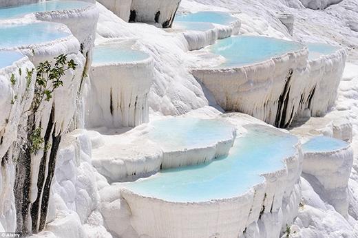 """Du khách sẽ hoàn toàn bị chinh phục bởi vẻ đẹp kì vĩ của Pamukkale – một cảnh quan thiên nhiên nằm trong thung lũng sông Menderes, thuộc tỉnh Denizli, Thổ Nhĩ Kỳ. Pamukkale nổi tiếng với những suối nước nóng chứa nhiều muối khoáng cacbonat được tích tụ, tạo thành những """"bậc thang"""" bằng đá vôi vô cùng ấn tượng. Suối nước nóng trong băng đá chính là điểm đặc biệt nhất của Pamukkale, và du khách khi đến Thổ Nhĩ Kỳ không thể bỏ qua kì quan tuyệt vời này. Ngoài ra, việc tắm nước nóng ở Pamukkale được cho là có công dụng chữa bệnh."""