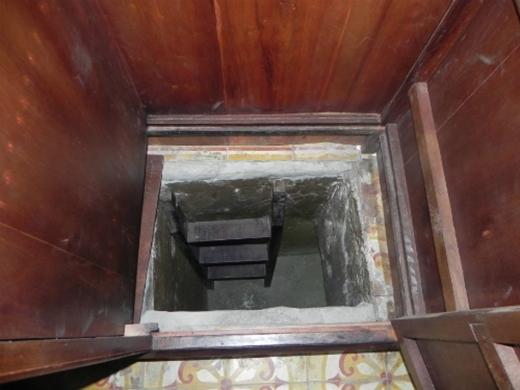 Lật tấm gỗ dưới đáy tủ sẽ thấy cầu thang xuống hầm.
