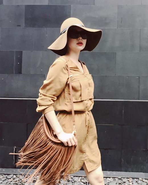 Chọn cách phối trang phục cùng tông màu, chiếc túi tua rua tạo nên tổng thể khá bụi bặm, cá tính cho Minh Hằng khi diện cùng váy lấy phom từ áo sơ mi. Chiếc mũ fedora hợp mốt cũng trở thành một phụ kiện không thể thiếu cho những trang phục ngày hè.