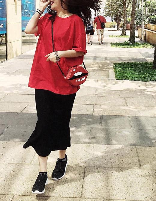 Cô diện món phụ kiện này cùng áo phông rộng thùng thình kết hợp chân váy đen phủ gối và mang giày thể thao cá tính, năng động.