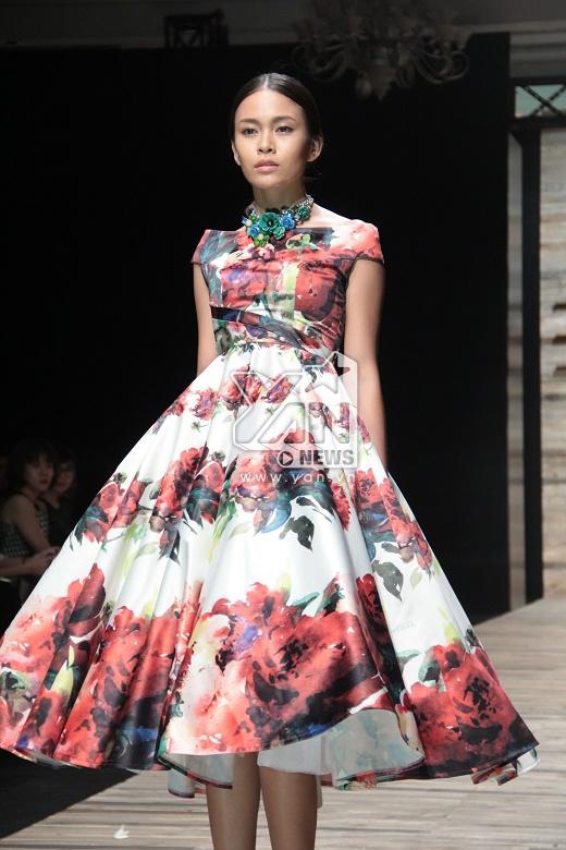 Điểm xuyết cho chiếc váy là vòng cổ to bản cũng được sử dụng họa tiết hoa màu xanh ngọc làm chủ đạo.