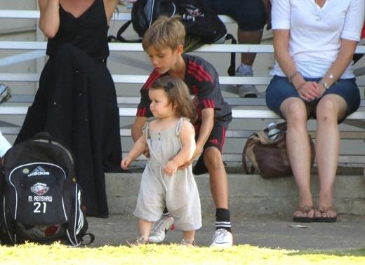 Romeo bế Harper khi cô bé đến sân bóng đá để chơi với anh mình.